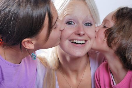 fond of children: A mother smiles as she receives a kiss on the cheek from her young daughters
