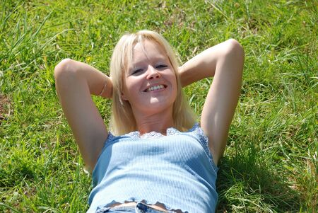 A beautiful young woman asleep in a grassy field  photo