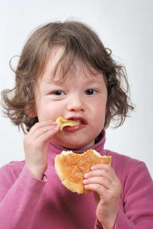 Una chica joven que come un bollo Foto de archivo - 18624283
