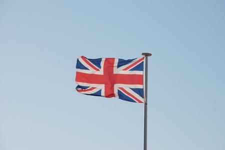Union Jack British flag flying on a weathered flag pole photo