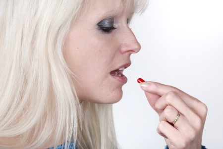 painkiller:  Woman holding a painkiller between finger Stock Photo