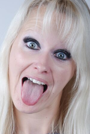 Young blonde woman sticking out her tongue photo