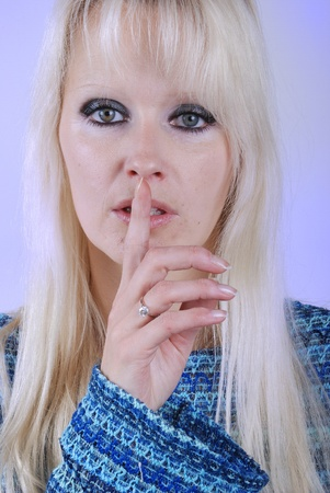 Young blond woman making silence finger over her mouth photo