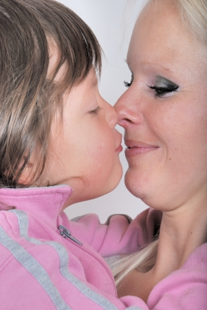 A mother as she receives a kiss from her young daughter photo