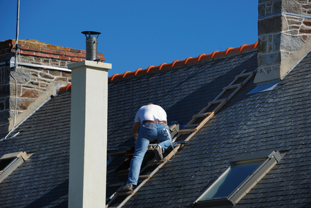 chimneys: Roofer working next to the chimney  Stock Photo