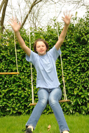 niño empujando: Una niña jugando en un columpio