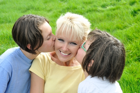 receives: A mother smiles as she receives a kiss on the cheek from her young daughters