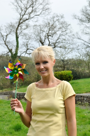 Portrait of blond woman with coloured pinwheel photo