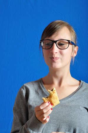 A  teen eating a chocolat bun
