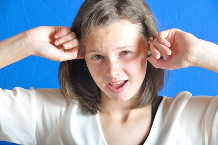 Teenage girl with her fingers in her ears. photo
