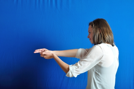 Teenage girl  miming gesture of holding a gun photo