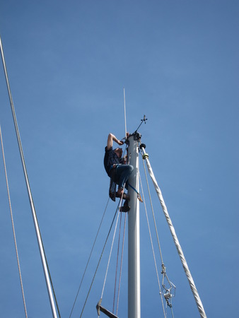 PLERIN, FRANCE-22MAY, 2017: Sailor mounted on the mast of his boat in the port of Pluie Editorial