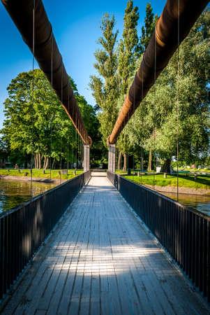A suspended bridge hangs above one of the canals in Bruges, Belgium. Banco de Imagens