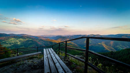 A bench offers a spectacular view over the soft forms of the Rhodope mountains in the south of Bulgaria, gilded by the last rays of the summer sun Stock Photo