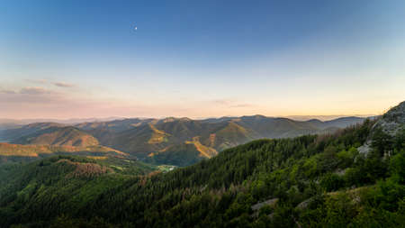 The moon watches from above as the last rays of the summer sun gild the soft forms of the Rhodope mountains in the south of Bulgaria