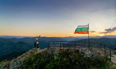 De vlag van Bulgarije golft bovenop de ruïnes van de vesting van Momchil in het Rhodope-gebergte, met de zon die op de achtergrond ligt.