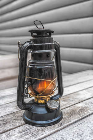 Old fashioned lantern on the wooden table. Vintage style metal lamp outdoor