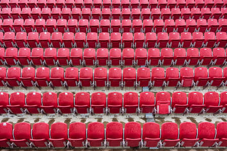 Picture of red colored tennis chairs in the line