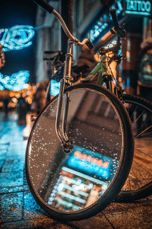 Picture of bicycle with mirror on the wheel at the night street.
