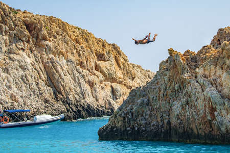 Young man jumping from the cliff into the ocean, summer fun adventure lifestyle 免版税图像