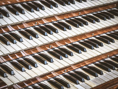 Close up view of a church pipe organ with four keyboards in the church