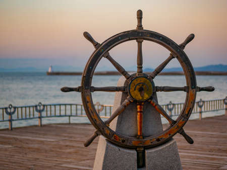 Captains steering wheel or rudder of an old wooden sailing ship in a port at sunset
