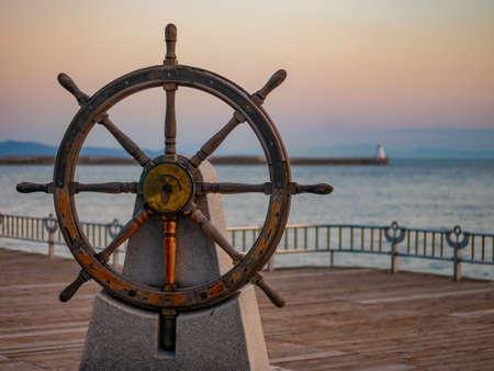 Kapitänslenkrad oder Ruder eines alten hölzernen Segelschiffs in einem Hafen bei Sonnenuntergang Standard-Bild