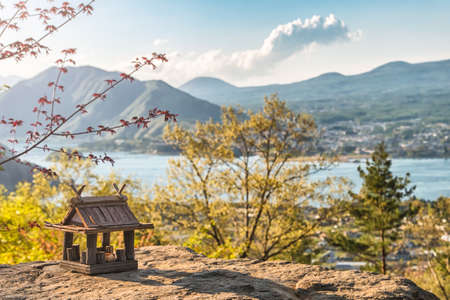 Idyllic landscape in the Japan with traditional wooden toy house and beautiful lake with mountains at the background at sunset