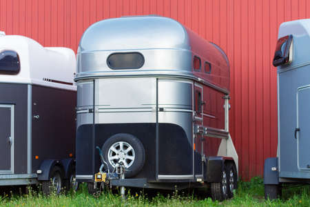 Picture of Several horse transportation trailers parked on the grass in front of red painted wooden house Stock Photo - 126577120