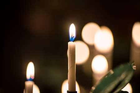 Muchas velas amarillas de cera de la iglesia encendidas en grande en un soporte especial Foto de archivo