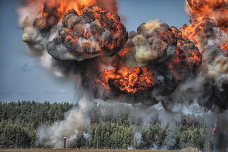 Image of Intense explosion with fire and black smoke and sky in the background