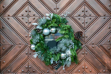 Large artificial circled wreath with knops and bead hangs during Christmas on door Imagens