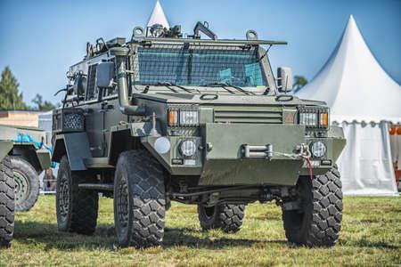Militärpatrouillenwagen auf grünem Gras. Kriegskonzept der Armee. Bild eines gepanzerten Fahrzeugs mit Waffe in Aktion.