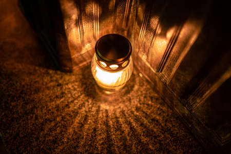 Jars with burning candles on stone surface at night Imagens