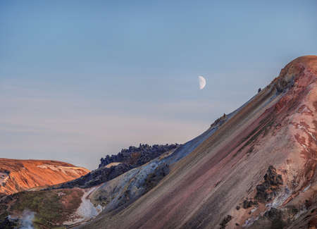 lunar landscape of Icelandic mountains with the moon in the blue sky