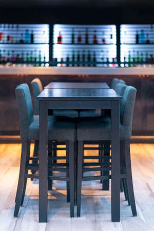 Picture of Black wooden bar table with chairs in the pub with bottles at the background