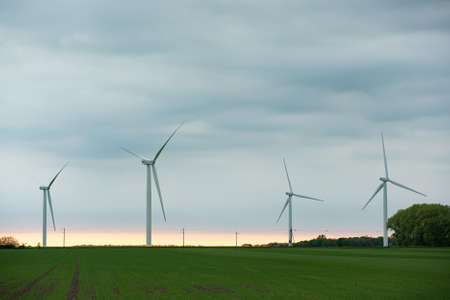 Image of Wind turbines on the green field at cloudy day Imagens