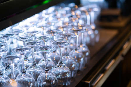 Image of Lines of wine glasses on the wooden table in the pub