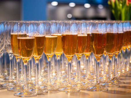 Image of a row of glasses filled with champagne are lined up ready to be served