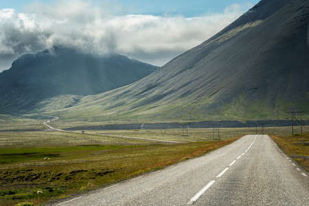 Image of Iceland road landscape with clouds and amply field