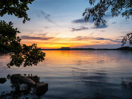 Image of Lakeside Sunset with trees and blue sky