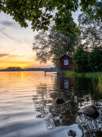 Image of Lakeside Sunset with trees, scandinavian wooden house and blue sky