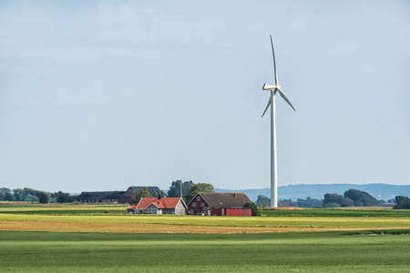 Picture of Swedish agriculture landscape with wind turbine in the field and wooden house