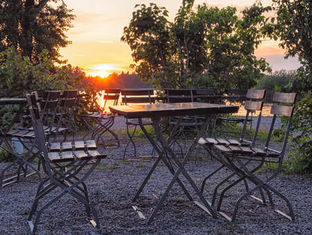 Image of Cafe table near the lake at evening, focus on table