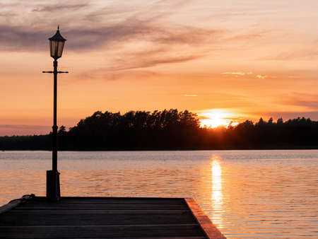 Image of Lakeside Sunset with wooden pier and trees at the background