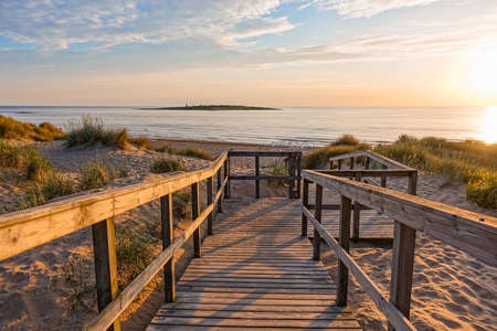 Image of Wooden path at Baltic sea over sand dunes with ocean view, sunset summer evening Stock Photo