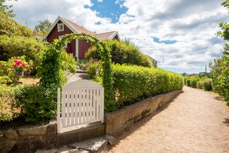 afbeelding van Smalle grindstrook naast rode en witte traditionele volkstuinhuisje met houten schutting en bloemen. Locatie Karlskrona in Zweden. Stockfoto