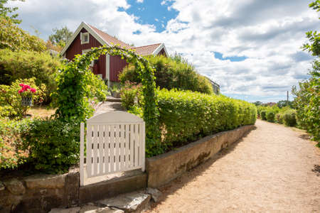 image of Narrow gravel lane beside red and white traditional allotment cabin with picket fence and flowers. Location Karlskrona in Sweden. Imagens
