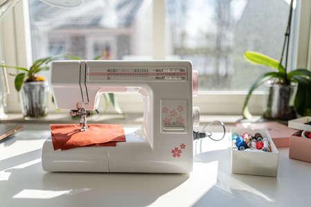 Nähmaschine auf dem weißen Tisch vor dem Fenster Standard-Bild
