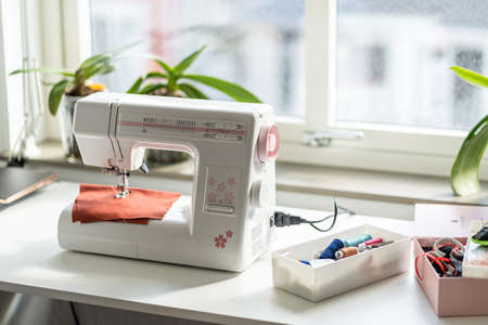 Image of Sewing machine on the white table in fron of the window